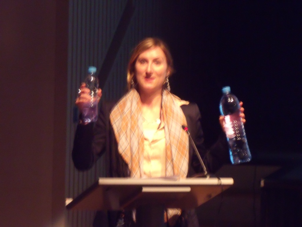Cara Flowers holding up two bottles of water.
