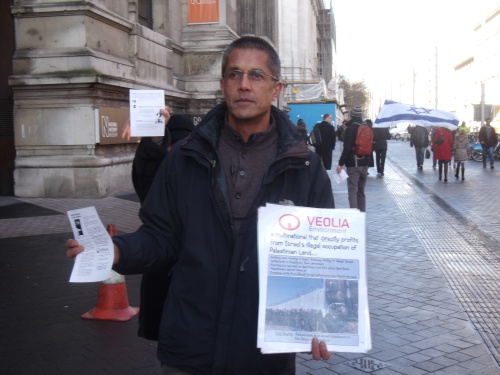 Salim Alam displays anti-Veolia literature (pro-Israel leaflet in background).