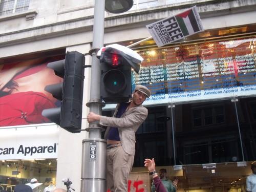 Courageous guy climbs a traffic light.