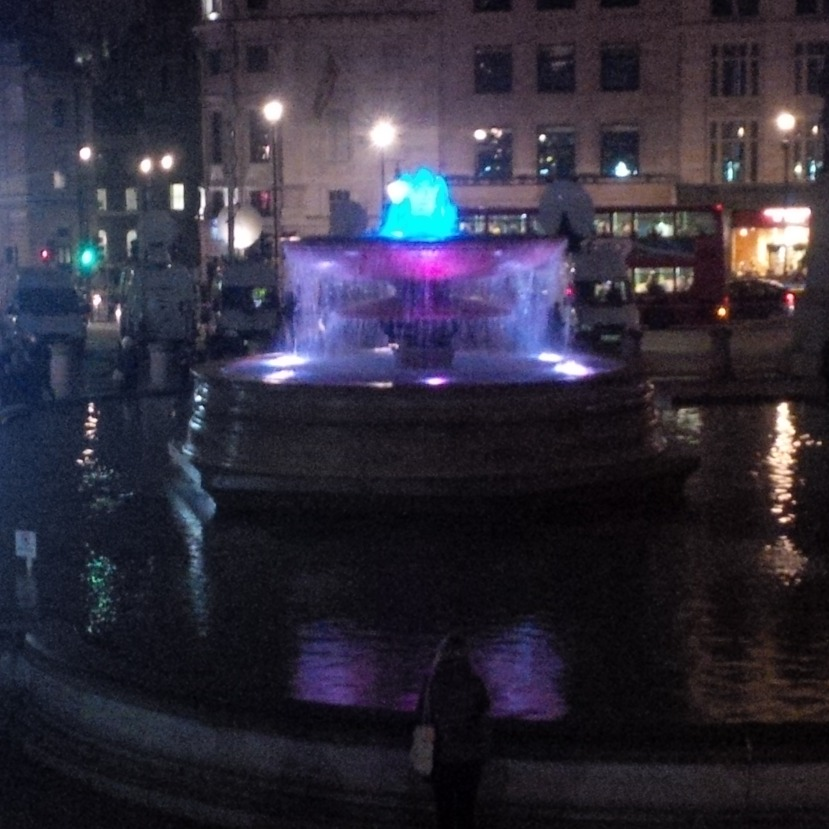 A fountain alternates red, white and blue.